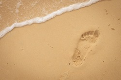 Copy space of footprint on sand beach and smooth wave texture background. Summer vacation and business travel freedom adventure concept. Vintage tone filter color style.