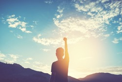 Copy space of man rise hand up on top of mountain and sunset sky abstract background. Freedom travel adventure and business victory concept. Vintage tone filter effect color style.