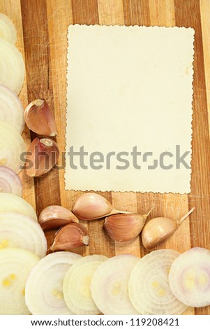 Copy space on a background of a wooden cutting board with an onions and garlic