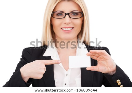 Copy space on her business card. Beautiful mature businesswoman pointing her business card and smiling while standing isolated on white