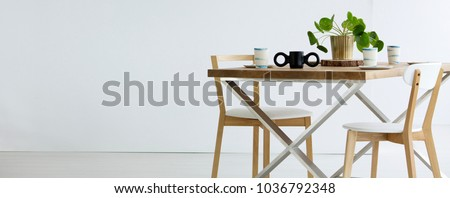 Copy space on white wall in empty dining room interior with chairs at wooden table #1036792348
