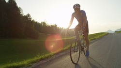 COPY SPACE, SUN FLARE: Pro road cyclist racing through the countryside in the afternoon. Active young man rides his bicycle through picturesque summer nature. Relaxing bicycle ride through the country