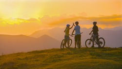 COPY SPACE Three young friends celebrate a successful cross country bike trip on a sunny summer evening in idyllic Slovenian mountains. Tourists ride bicycles up to edge of a grassy hill and high five