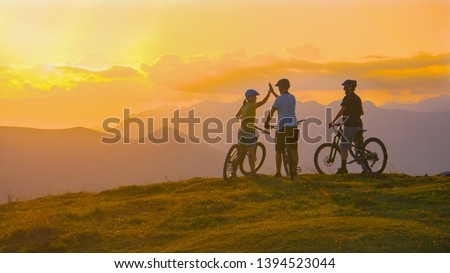 COPY SPACE Three young friends celebrate a successful cross country bike trip on a sunny summer evening in idyllic Slovenian mountains. Tourists ride bicycles up to edge of a grassy hill and high five #1394523044