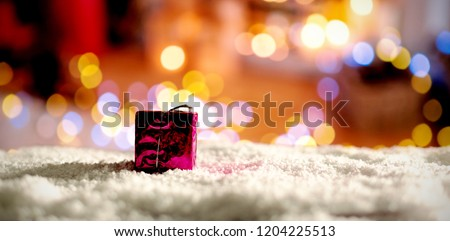 Copy space with gift and snow against defocused of christmas tree lights and fireplace #1204225513