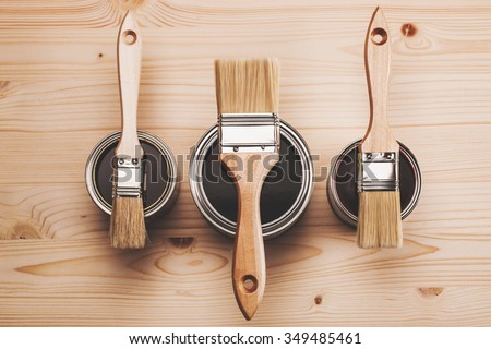 Copy space with three paint brushes on three cans lying on wooden clean table. Top view Foto d'archivio ©