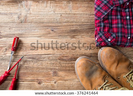 Copy space work tool equipment - working shoes, dress and screwdrivers on wood table. Top view. Stock photo ©