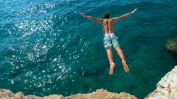 COPY SPACE: Young man on relaxing summer vacation does cliff diving on a hot and sunny day. Cinematic shot of an athletic Caucasian man jumping off a rocky ledge and into the glistening blue ocean.