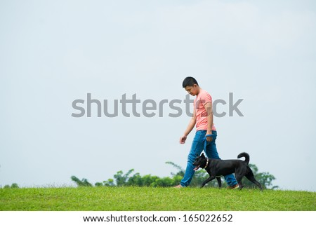 Photo of Copy-spaced image of a dog-owner walking with his pet on the green lawn