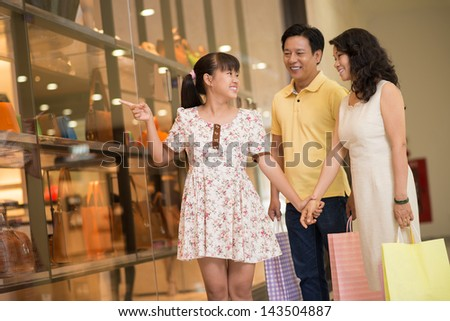 Copy-spaced image of a young daughter asking her mother to buy something in the store