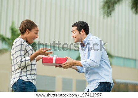 Copy-spaced image of an excited couple where a boyfriend presenting his girlfriend with a giftbox on the foreground