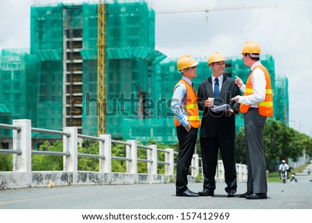Copy-spaced image of modern engineers discussing something outside