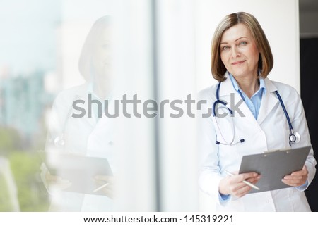 Copy-spaced portrait of a friendly general practitioner holding a medical record