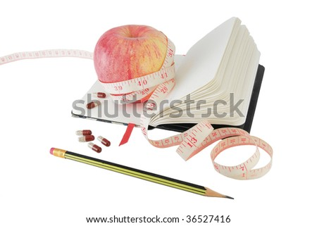 Copybook with apple, measure tape and vitamin pills to aid effective diet