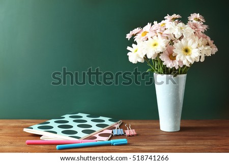 Copybooks and flowers on teacher\'s desk