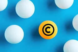 Copyright icon on yellow ball on blue background. Property and intellectual rights protection.