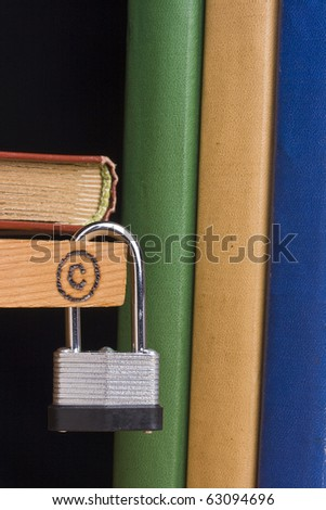 Copyright symbol on a piece of wood attached to a lock by a couple of books.