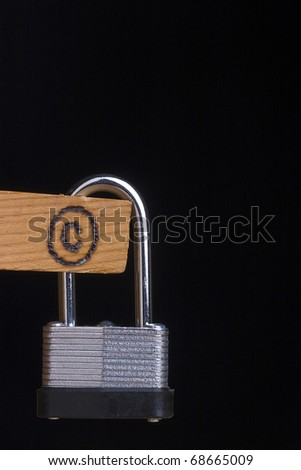 Copyright symbol on a piece of wood attached to a lock on a black background.