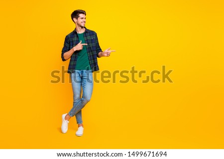 Copyspace full length body size photo of cheerful charming cute guy wearing denim showing with his forefingers at empty space isolated over vivid color background