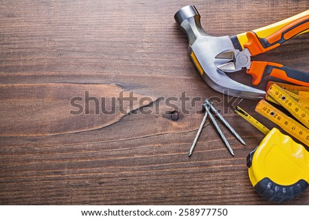 copyspace image claw hammer nails tapeline wooden meter nippers on vintage board construction concept