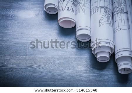 copyspace image rolls of blueprints on blue board.