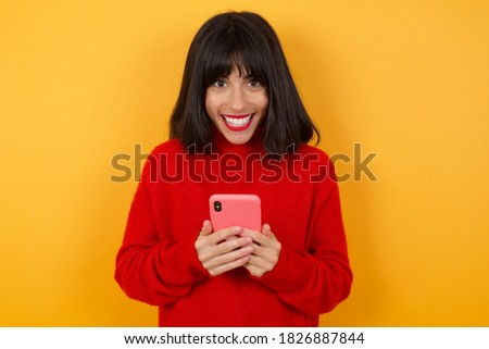 Copyspace photo of cheerful nice cute charming Caucasian brunette woman wearing red casual sweater isolated over yellow background holding phone in his hands while stock photo