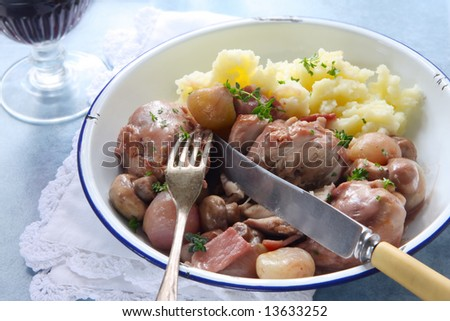 Coq au Vin, in old enamel bowl, with lacy napkin and vintage cutlery.  Traditional French chicken casserole, with mashed potato.