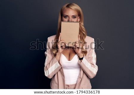 Coquette portrait. The girl covered part of her face with a tablet. A woman with a notebook and pen. A girl with beautiful eyes on a grey background