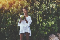 Coquettish young cute Brazilian female in front of quickset hedge of cactuses with coconut is quenching her thirst; black flirtatious girl is drinking coco water while standing near wall of cactuses