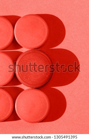 Coral color  plastic bottle caps on a coral background, the round caps are in two rows , monochromatic effect #1305491395