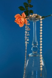 Coral colored rose on top the bottom of a glass with rhinestones and pearls dangling in an elegant fashion with a bold blue background