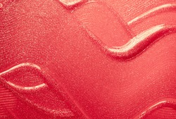 Coral red lip gloss with shimmer textured background