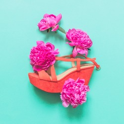 coral sandals decorated with fuchsia peonies flowers on a turquoise background