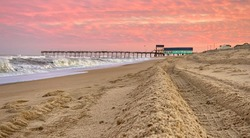 Coral sunset over the turquoise pier house at Avalon Pier in Kill Devil Hills, North Carolina.