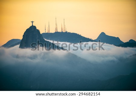 Corcovado mountain Christ the Redeemer standing in golden sunset above swirling mist clouds Rio de Janeiro Brazil #294682154