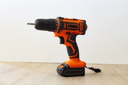 Cordless combi drill for used as normal drill, impact drill and screw driver. Cordless impact screwdriver and self-tapping screws for wood on white wooden background. Selective focus