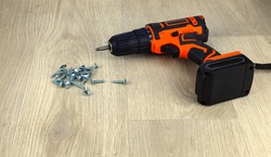 Cordless combi drill for used as normal drill, impact drill and screw driver. Cordless impact screwdriver and self-tapping screws for wood on white wooden background.