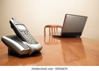 A stock photo of a cordless phone and laptop sit on an empty table.
