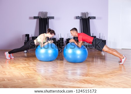 Core / balance training. Couple doing plank exercise using exercise balls