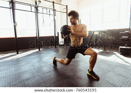 Core strength and stability workout. Fit and muscular man exercising with medicine ball at gym.