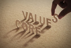 CORE VALUE wood word on compressed or corkboard with human's finger at S letter.