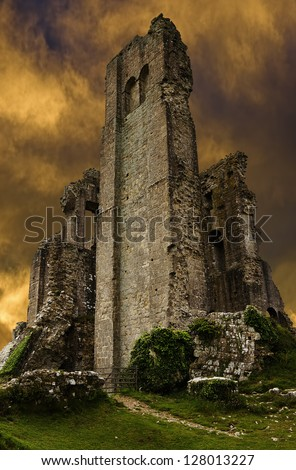 Corfe Castle ruins in evening with dark stormy sunset sky