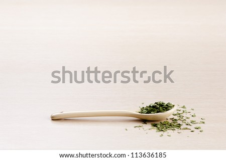 Coriander in a spoon with some spilled over the wooden background