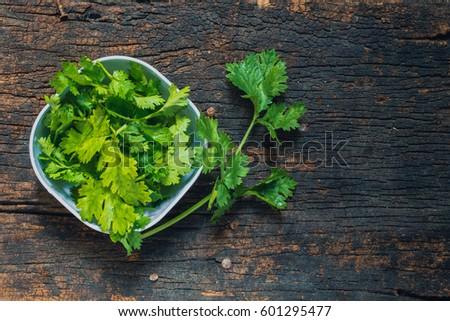 Coriander leaves, fresh green cilantro on wooden background, Food herbal aroma ingredient on dark wood. #601295477