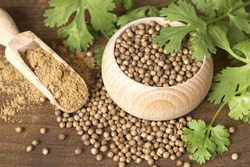 Coriander seeds and leaves on a wooden background