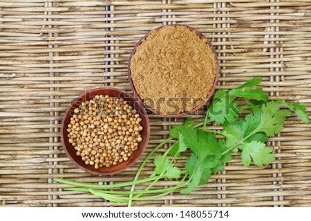 Coriander seeds, coriander powder and fresh coriander on wicker surface