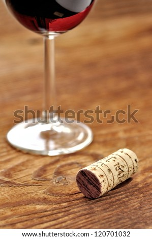 Cork and glass of italian red wine on a table in oak, closeup, selective focus
