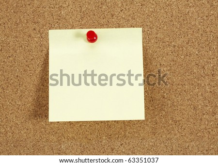 Cork board with blank yellow paper note