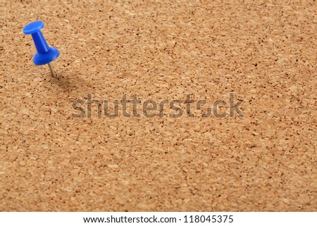 Cork board with blue pin on left top