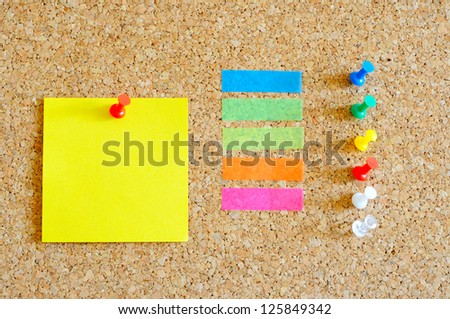 Cork board with multiple colorful objects on it